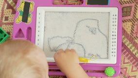 Un ragazzo piacevole di 2 anni attinge un tavolo da disegno magnetico Ha grandi figure incomprensibili Il bambino prova molto dur stock footage