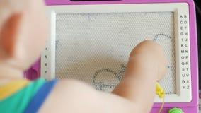 Un ragazzo piacevole di 2 anni attinge un tavolo da disegno magnetico Ha grandi figure incomprensibili Il bambino prova molto dur archivi video