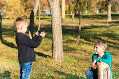 Un ragazzo prende le immagini sullo smartphone di suo fratello nel parco un giorno soleggiato fotografie stock