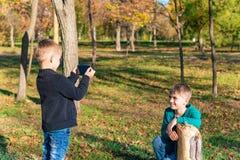 Un ragazzo prende le immagini sullo smartphone di suo fratello nel parco un giorno soleggiato immagine stock libera da diritti