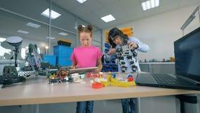 Un ragazzo ripara un robot mentre una ragazza lavora con una compressa in una stanza del laboratorio Concetto moderno di istruzio video d archivio