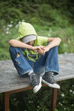 Un ragazzo senza tetto si siede su un banco con la sua testa inchinata Fotografie Stock