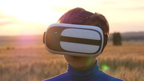 Un ragazzo sta in un giacimento di grano al tramonto in vetri virtuali Fotografia Stock Libera da Diritti