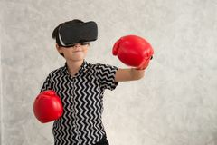 Un ragazzo sta giocando il gioco di pugilato con la cuffia avricolare di realtà virtuale 3D Fotografia Stock