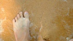 Un ragazzo sta prendendo una sabbia sul piede stock footage