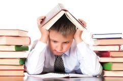Un ragazzo stanco e ritardante dello scolaro si siede in una biblioteca con i libri ed impara le lezioni Riluttanza imparare immagini stock libere da diritti