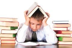 Un ragazzo stanco e ritardante dello scolaro si siede in una biblioteca con i libri ed impara le lezioni Riluttanza imparare fotografie stock libere da diritti