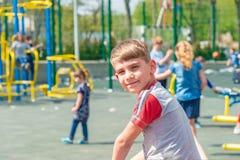 Un ragazzo sul campo da giuoco, un ritratto di un bambino contro il contesto delle oscillazioni dei bambini e divertimenti immagine stock