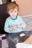 Un ragazzo sveglio di tre anni che contribuiscono a cuocere in cucina domestica, Fotografie Stock