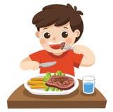 Un ragazzo sveglio sta mangiando la bistecca con le verdure Fotografia Stock