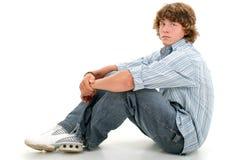 Un ragazzo teenager attraente di sedici anni in vestiti casuali sopra briciolo Fotografia Stock