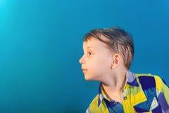 Un ragazzo in una camicia colorata con un fondo blu pende dentro e guarda avanti immagini stock