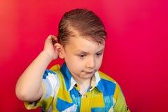 Un ragazzo in una camicia colorata sta graffiando la sua testa nel suspense, su un fondo rosso fotografia stock libera da diritti