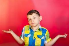 Un ragazzo in una camicia di colore scrolla le spalle e sparge le sue armi al lato, su un fondo rosso immagini stock
