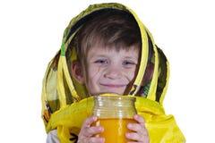 Un ragazzo in una maschera gialla dalle api, tenenti un barattolo di miele ed esaminanti la macchina fotografica nello studio, su fotografie stock libere da diritti