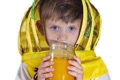 Un ragazzo in una maschera gialla dalle api, tenenti un barattolo di miele ed esaminanti la macchina fotografica nello studio, su fotografia stock libera da diritti