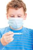 Un ragazzo in una maschera protettiva con il termometro a disposizione Fotografia Stock