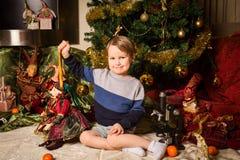 Un ragazzo in un vestito luminoso sta sedendosi vicino all'albero del nuovo anno con le bambole fatte a mano fotografie stock libere da diritti