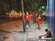 Un ragazzo vietnamita che vende i tessuti su una via fotografia stock