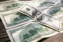Un raggio di sole sulle 100 banconote del dollaro, diffusione fuori sulla superficie di legno invecchiata Fotografia Stock