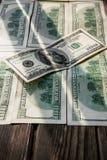 Un raggio di sole sulle 100 banconote del dollaro, diffusione fuori sulla superficie di legno invecchiata Fotografia Stock Libera da Diritti