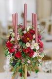 Un ramo agraciado de flores frescas y una vela en una tabla que se casa fotografía de archivo libre de regalías