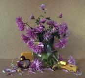 Un ramo de asteres púrpuras en un jarro transparente con agua, cerca de los pedazos de la mentira del jarro de queso amarillo y d Foto de archivo