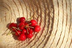 Un ramo de cerezas frescas en un sombrero del sol Fotos de archivo