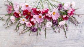 Un ramo de cosmea o de cosmos de las flores blancas con la cinta en los tableros blancos Flores amarillas del jardín sobre backgr Fotos de archivo