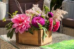 Un ramo de diversas flores en una caja de madera foto de archivo