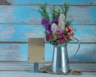 Un ramo de flores color de rosa artificiales adentro galvaniza puede y papel Imágenes de archivo libres de regalías
