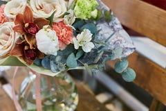 Un ramo de flores en un florero de cristal en un fondo de tableros de madera en una escala marrón caliente Fotografía de archivo libre de regalías