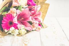 Un ramo de flores de un lirio, de un gerbera, de rosas blancas y de un alstroemeria en una tabla de madera blanca Un día de fiest Imagenes de archivo