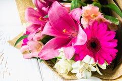 Un ramo de flores de un lirio, de un gerbera, de rosas blancas y de un alstroemeria en una tabla de madera blanca Un día de fiest Imágenes de archivo libres de regalías