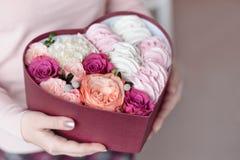 Un ramo de flores y de melcochas en una caja de regalo de corazón en manos femeninas Concepto congratulatorio, venta foto de archivo
