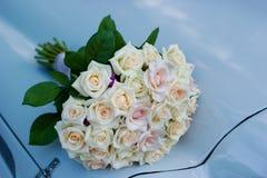 un ramo de la boda miente en un coche azul hermoso foto de archivo libre de regalías