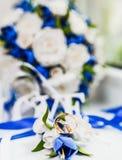 Un ramo de la novia de las rosas y de los anillos de bodas blancos y azules del oro imágenes de archivo libres de regalías