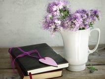 Un ramo de las flores púrpuras, libros en una tabla de madera vieja foto de archivo libre de regalías
