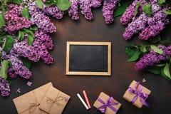 Un ramo de lilas con el tablero de tiza, caja de regalo, sobre del arte en fondo oxidado fotografía de archivo