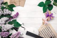 Un ramo de lilas con el violín, la caja de regalo y la hoja de música en una tabla de madera blanca Wiev superior con el espacio  fotos de archivo