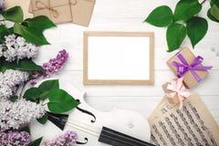 Un ramo de lilas con el violín, marca el tablero, la caja de regalo y la hoja de música con tiza en una tabla de madera blanca Wi imagen de archivo libre de regalías