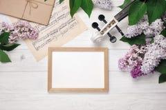 Un ramo de lilas con el violín, el tablero de tiza y la hoja de música en una tabla de madera blanca Wiev superior con el espacio fotografía de archivo libre de regalías