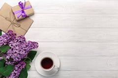 Un ramo de lilas con la taza de té, caja de regalo, sobres del arte, una nota del amor sobre los tableros blancos foto de archivo