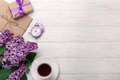 Un ramo de lilas con la taza de té, de despertador, de caja de regalo y de sobre del arte en los tableros blancos imagen de archivo