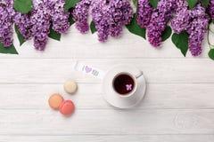 Un ramo de lilas, de taza de té, de nota del amor y de macarons en una tabla de madera blanca foto de archivo