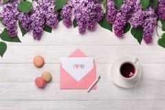 Un ramo de lilas, de taza de té, de nota del amor y de macarons en una tabla de madera blanca fotos de archivo libres de regalías