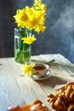 Un ramo de narcisos amarillos todavía está en un florero y una taza de té en la tabla en la vida de la mañana imagenes de archivo