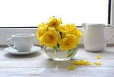 Un ramo de rosas amarillas y una taza de café se colocan en el alféizar Foto de archivo libre de regalías