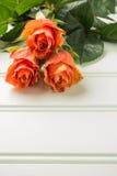 Un ramo de rosas anaranjadas en la tabla de madera Copie el espacio Foto de archivo