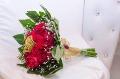 Un ramo de rosas frescas rojas y de rosas artificiales de oro con la cinta, gotas y hojas del verde en una silla blanca Imagenes de archivo